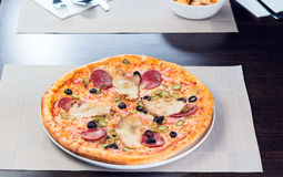 Italian pizza. With ham tomato and olives Stock Image