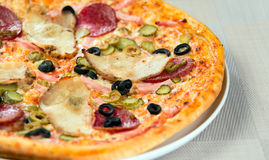 Italian pizza. With ham tomato and olives Royalty Free Stock Images