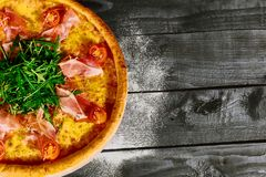 Italian pizza with ham, tomatoes and herbs on a wooden table stock photography
