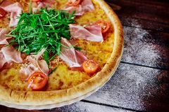 Italian pizza with ham, tomatoes and herbs on a wooden table �lose up royalty free stock photo