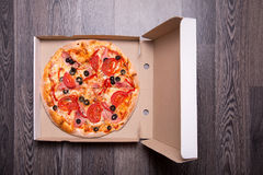 Italian pizza with ham, tomatoes, and olives in box Royalty Free Stock Photo