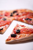 Italian pizza with ham, tomatoes and olives with a slice removed Stock Image