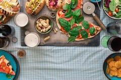 Italian pizza, hot dog, salad, wine, lager, snacks to beer. Italian pizza, hot dog grilled, salad, red wine, lager and snacks to beer, top view with border stock photography