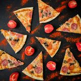 Italian pizza with ingredients. Flat lay, top view. Pizza chips pattern on dark table stock photography