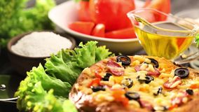Italian pizza and ingredients served on the black wooden table stock footage