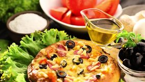 Italian pizza and ingredients served on the black wooden table stock video