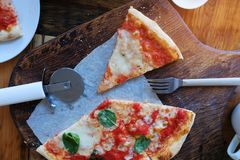 Italian pizza Margarita with mozzarella cheese, tomatoes and fresh Basil on the table in a cafe or restaurant. Next to a knife stock image