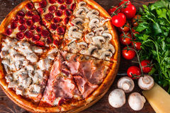 Italian pizza with meat and sausage on wood table. Yummy baked pizza with mushrooms, ham, chicken and sausages on wooden background with ingredients, top view Royalty Free Stock Images