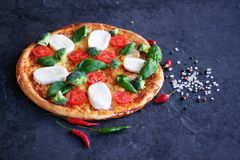 Italian pizza with Mozzarella cheese, tomatoes, broccoli, Spices and fresh basil. Pizza on stone background stock images