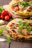 Italian pizza with parmesan cheese, prosciutto and arugula Stock Images