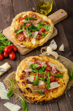 Italian pizza with parmesan cheese, prosciutto and arugula Royalty Free Stock Image