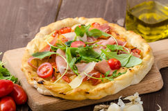 Italian pizza with parmesan cheese, prosciutto and arugula Royalty Free Stock Photo