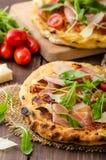Italian pizza with parmesan cheese, prosciutto and arugula Stock Photo