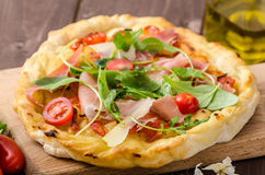 Italian pizza with parmesan cheese, prosciutto and arugula Royalty Free Stock Photos