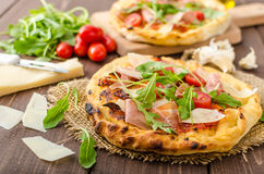 Italian pizza with parmesan cheese, prosciutto and arugula Stock Photos