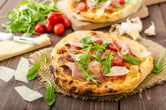 Italian pizza with parmesan cheese, prosciutto and arugula Royalty Free Stock Images