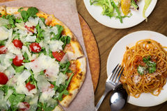 Italian pizza and pasta. Served on the wooden table Royalty Free Stock Photos