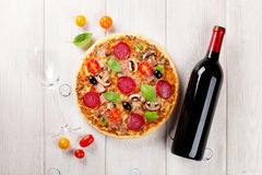 Italian pizza with pepperoni, tomatoes, olives, basil and red wi Royalty Free Stock Images