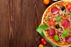Italian pizza with pepperoni, tomatoes, olives and basil stock images