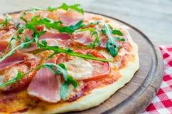Italian pizza with prosciutto and arugula stock images