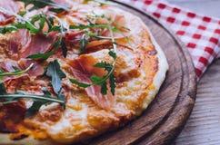 Italian pizza with prosciutto and arugula royalty free stock photo