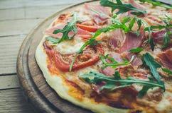 Italian pizza with prosciutto and arugula stock photo