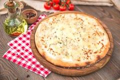 Italian Pizza quattro fromaggi. On a wooden board Stock Photography