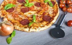 Italian pizza. Italian salami pizza  with basil and cherry tomatoes Stock Photography