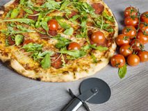 Italian pizza. Italian salami pizza  with basil and cherry tomatoes Stock Images