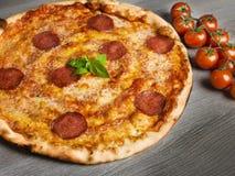 Italian pizza. Italian salami pizza with mail and cherry tomatoes Royalty Free Stock Photos