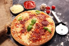 Italian pizza with salami, peperoni - with melted cheese, red tomatoes and green basil on a table decorated by cheese, tomato and. Italian pizza with salami stock image