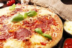 Italian pizza with salami, peperoni - with melted cheese, red tomatoes and green basil on a table decorated by cheese, tomato and. Italian pizza with salami royalty free stock image