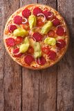 Italian pizza with salami and pepper vertical top view, rustic Royalty Free Stock Photo