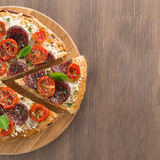 Italian pizza with salami and tomatoes on wooden background Stock Images