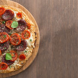 Italian pizza with salami and tomatoes on wooden table Royalty Free Stock Photos
