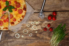 Italian pizza with sausage, cheese and tomato. On a wooden table there is some pizza and near there are a few tomato, green onion and a knife Royalty Free Stock Images