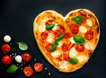 Italian pizza in the shape of heart on Valentine`s Day Royalty Free Stock Photo