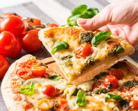Italian pizza on tablecloth with hand Royalty Free Stock Photo