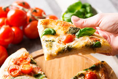 Italian pizza on tablecloth with tomatoes and hand close up Royalty Free Stock Photography