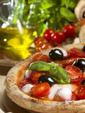 Italian pizza with tomato, mozzarella and olives. Italian pizza with tomato, mozzarella, basil and olives Royalty Free Stock Images
