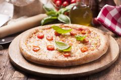 Italian pizza with tomato topped with melted golden cheese, herb Stock Image