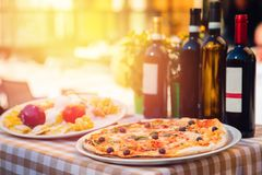 Italian pizza with tomatoes, mozzarella cheese, basil, black olives. In background, wine and highlight of light at. Sunset stock photo
