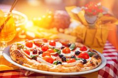 Italian pizza with tomatoes, mozzarella cheese, basil, black olives. In background, wine and highlight of light at. Sunset royalty free stock photo