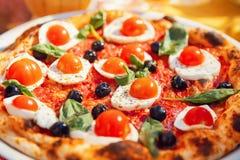 Italian pizza with tomatoes, mozzarella cheese, basil, black olives on board. Concept restaurant.  stock photo