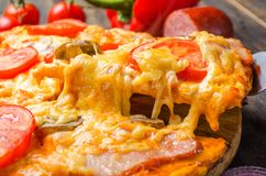 Italian pizza with tomatoes and mushrooms on a wooden board royalty free stock image