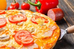 Italian pizza with tomatoes and mushrooms on a wooden board stock photography