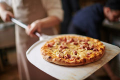 Italian pizza. Traditional pizza being taken out of oven Stock Image