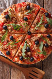 Italian pizza with tuna, olives and arugula close-up. Vertical t Royalty Free Stock Image
