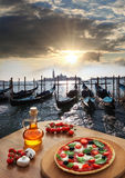 Italian pizza in Venice against canal, Italy Stock Photo