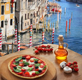 Italian pizza in Venice against canal, Italy Stock Photos